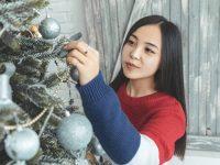 charming asian woman decorating christmas tree