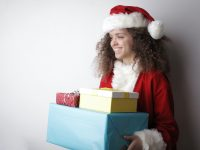 delighted woman in santa claus costume with christmas gifts