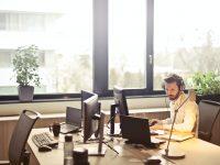 man with headphones facing computer