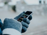 wearing gloves holding a cellphone